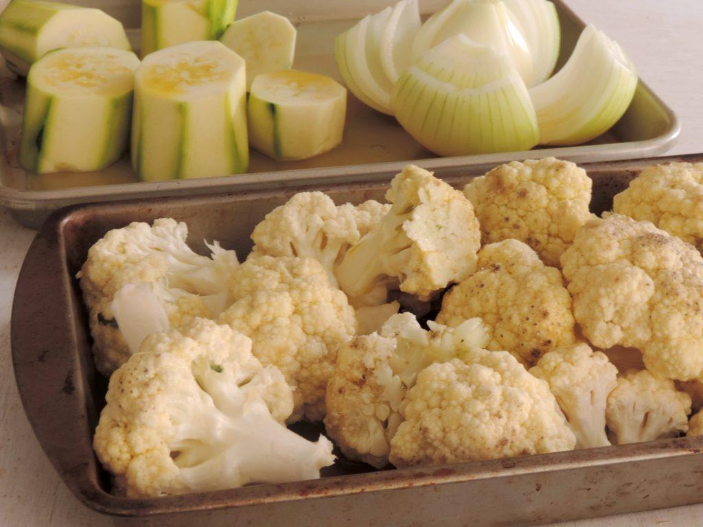 Aspecto de dos bandejas con vegetales pelados y listos en bandejas para transferir al horno. Ingredientes de la salsa bechamel saludable.