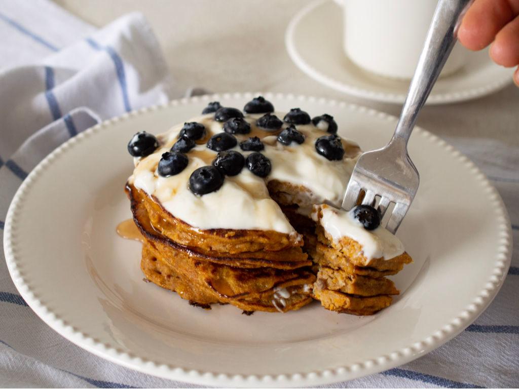 Torre de pancakes de auyama servido con yogur griego y arándanos, con un tenedor.