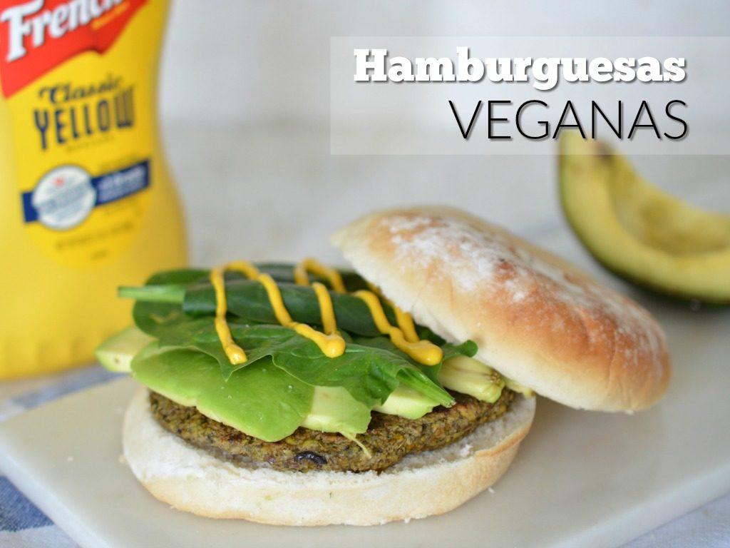 Plato de hamburguesas veganas servidas en pan blanco con aguacate, mostaza y espinaca.