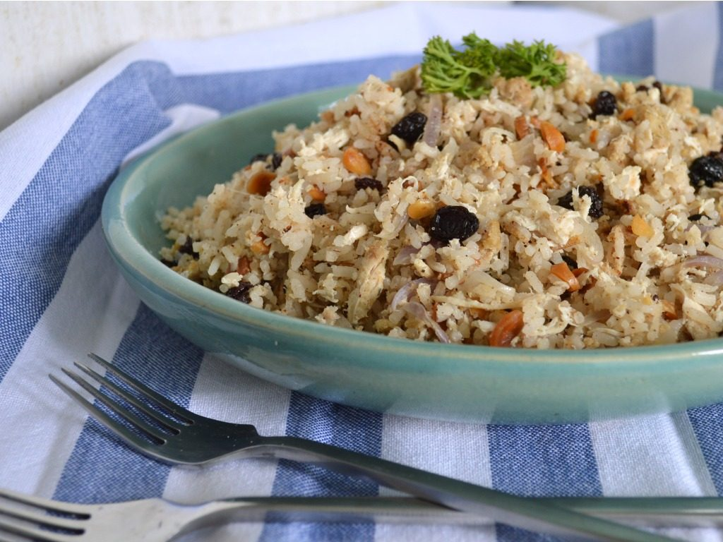 Plato azul de arroz árabe de almendras con un par de tenedores.
