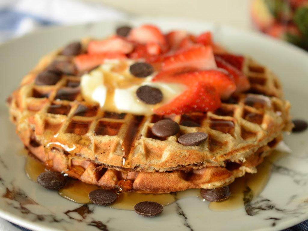 Primer plano de waffles de banano con chips de chocolate, de ellos cae miel de maple.
