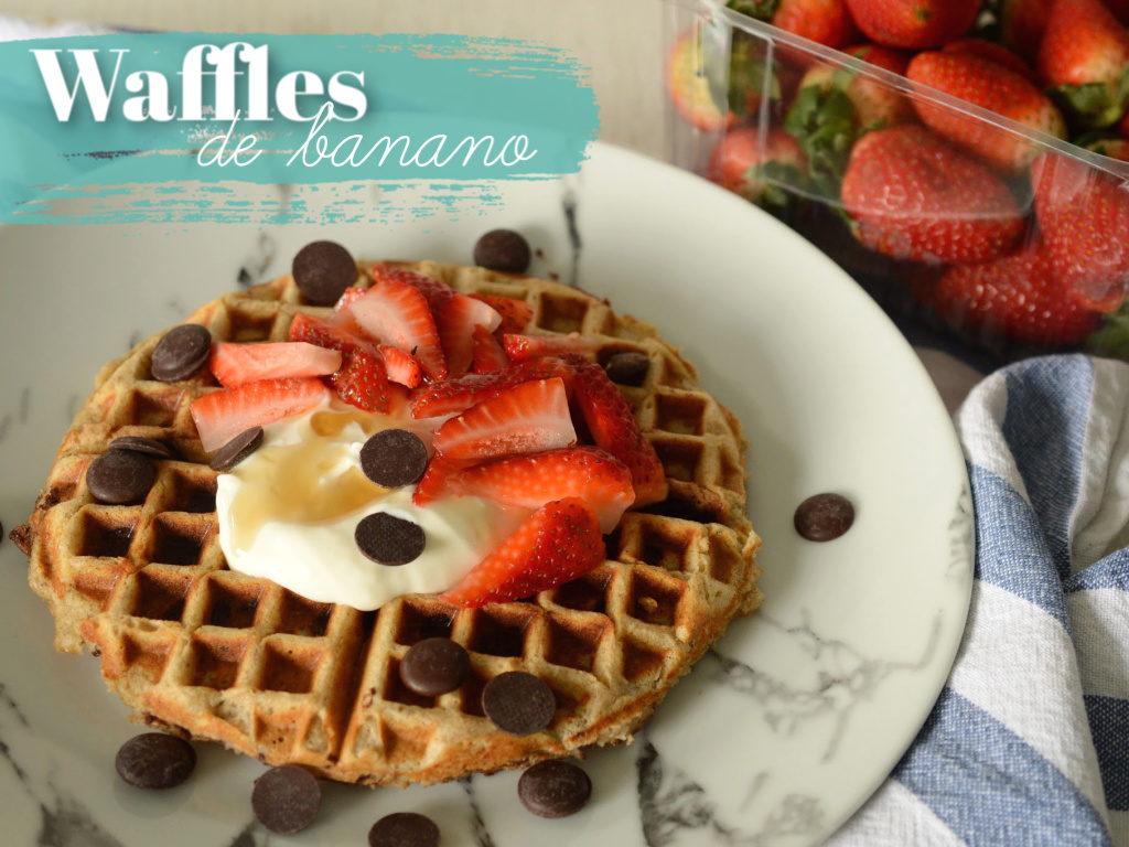 Waffles de banano con chips de chocolate decorados con fresas frescas y yogur griego.