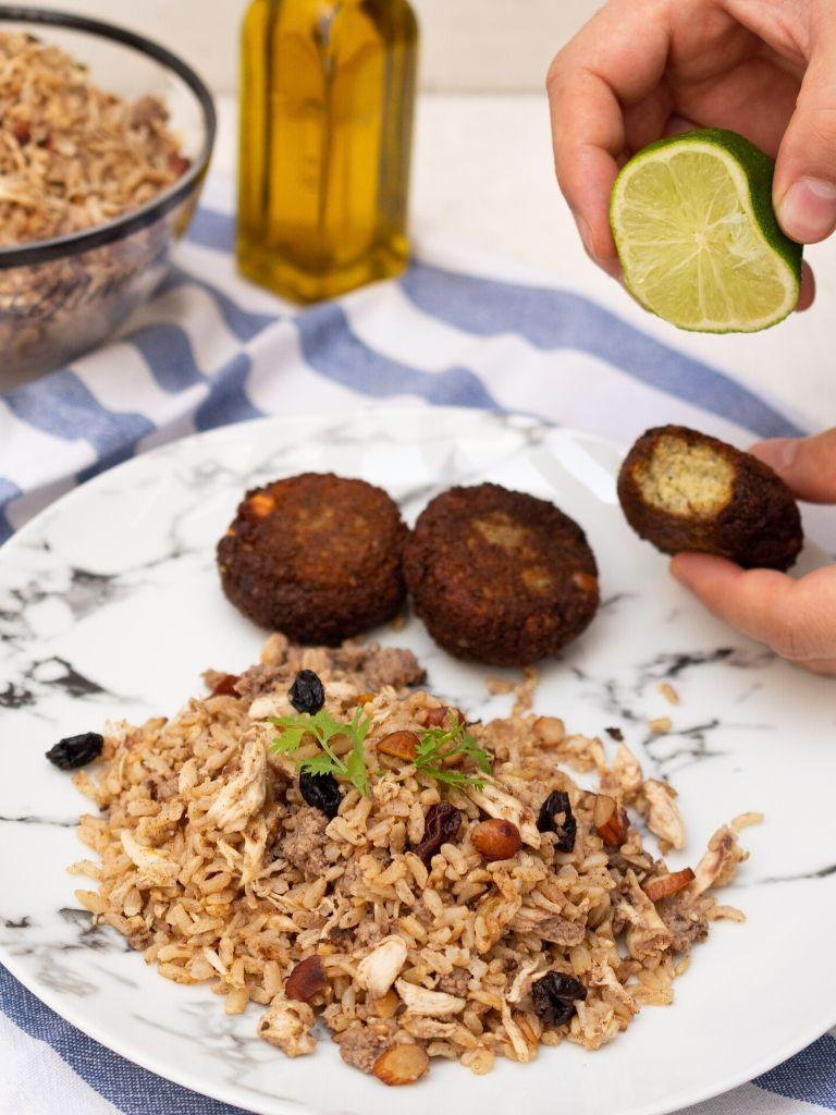 Arroz árabe de almendras, servido con falafel, sobre plato blanco con vetas negras.
