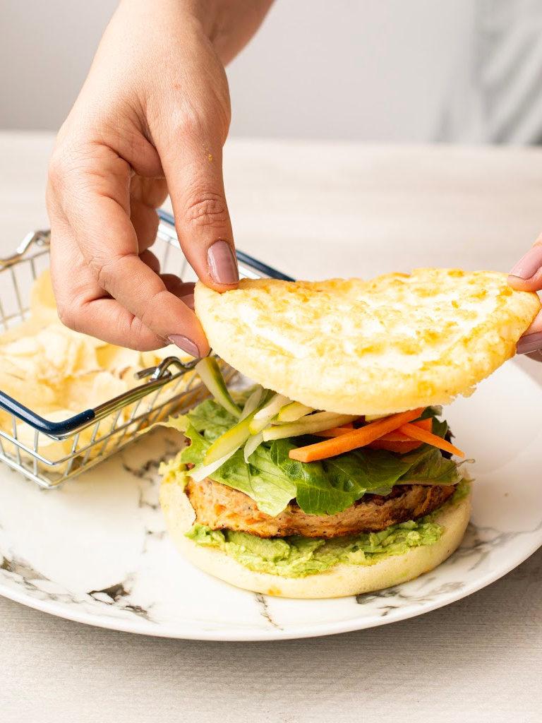 Hamburguesa de salmón con verduras y papas fritas.