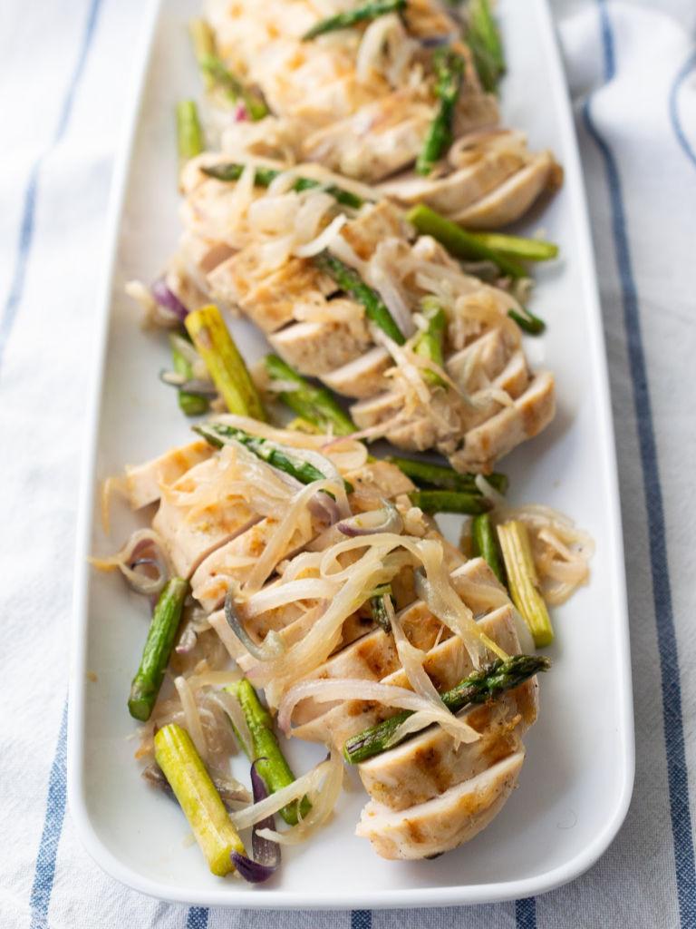 Foto de pechuga de pollo jugosa horneada y servida con vegetales.