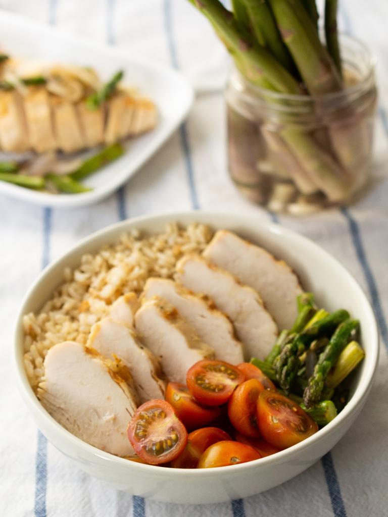 Plato hondo con pechuga de pollo jugosa, arroz y vegetales.