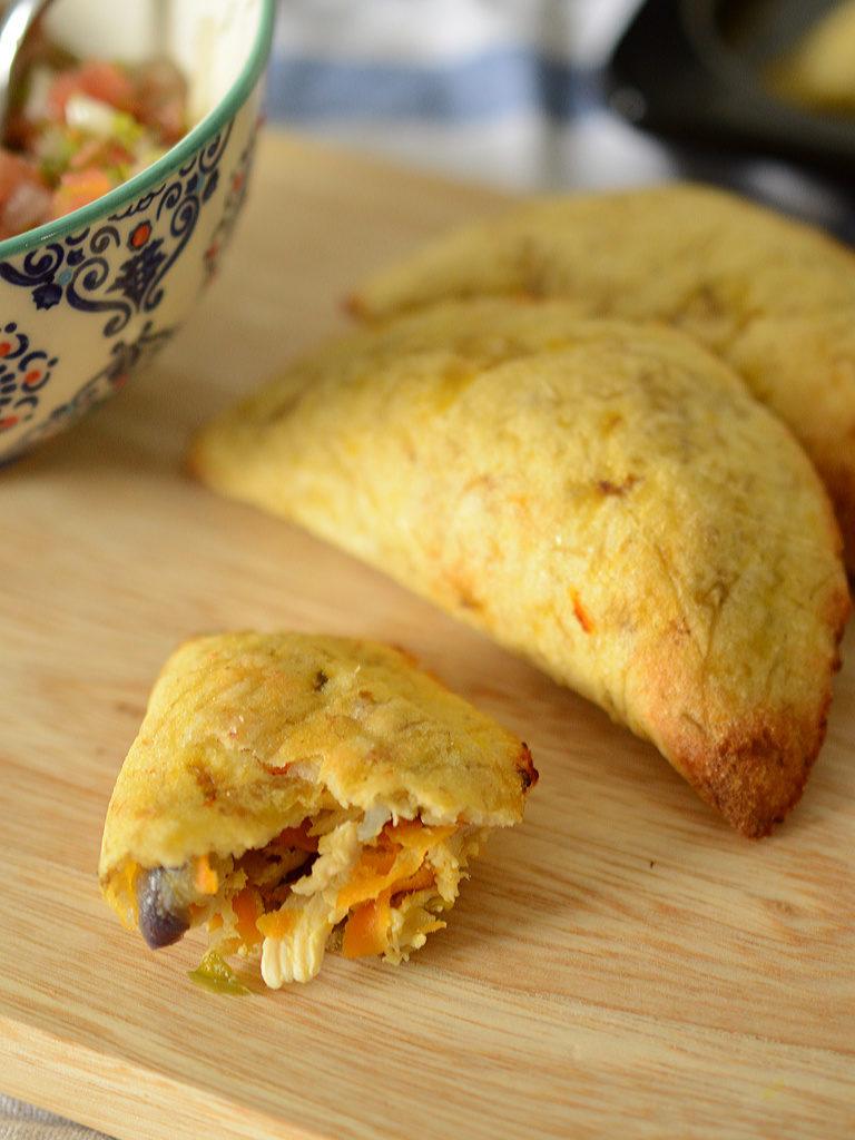 Detalle de unas empanadas de plátano, se ve el relleno de pollo desmechado y vegetales.