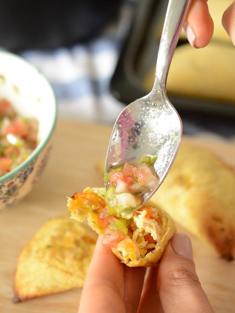 Primer plano de unas empanadas de plátano abiertas, encima se posa una cuchara llena de ají hecho con tomate, cebolla y cilantro.
