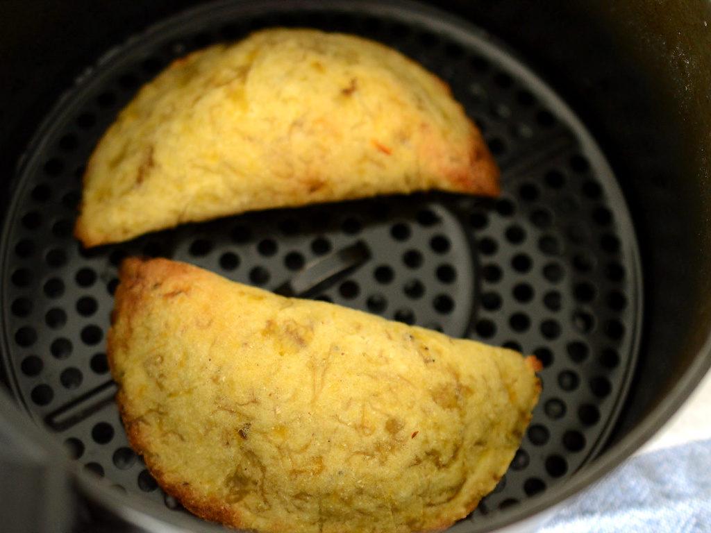 Empanadas de plátano listas en el la olla de una freidora de aire.