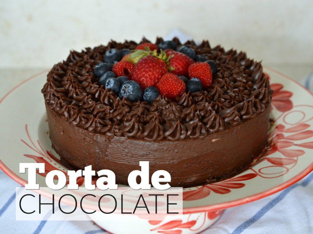 Foto de una torta cubierta de chocolate con frutas encima.