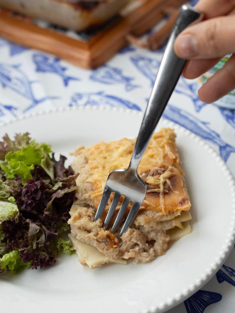Una porción de lasaña de atún servida con ensalada fresca.