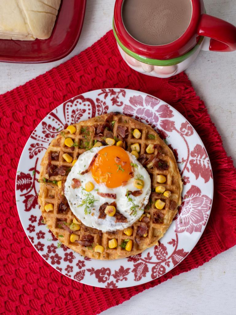 Foto cenital de unos waffles navideños de buñuelo servidos en un plato rojo con blanco.