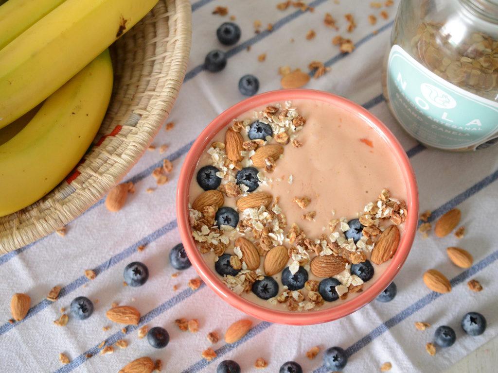 Smoothie bowl de papaya y banano con granola, avena y arándanos.