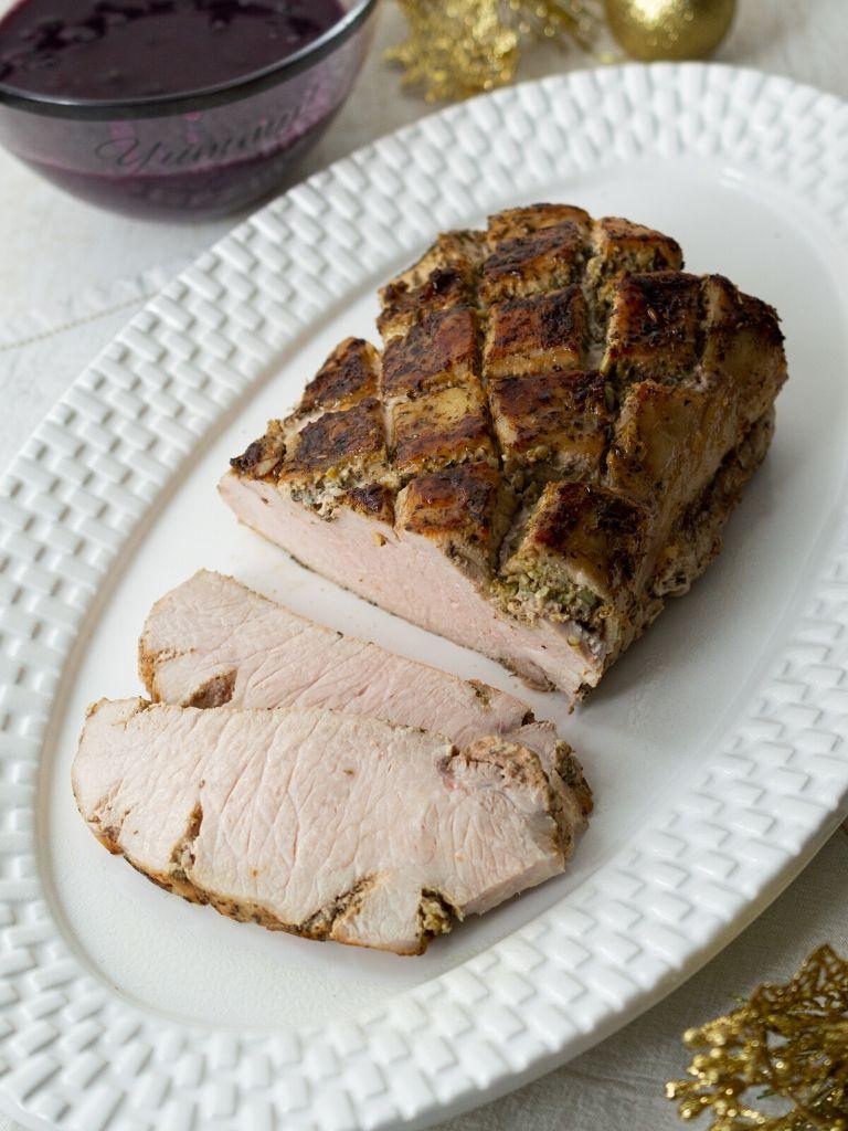 Lomo de cerdo servido en un plato grande, acompañado de salsa de arándanos.