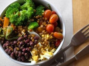 Tazón de ensalada con brócoli, tomate cherry, huevo duro y lentejas crocantes.