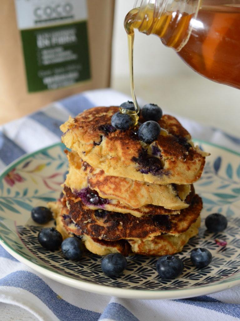 Torre de pancakes de harina de coco con arándanos, cae un chorro de miel encima.