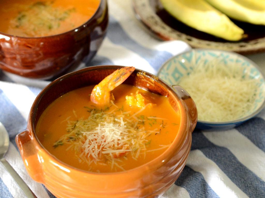 Tazón con una sopa amarilla de la que sobresale un langostino, espolvoreada con queso parmesano.