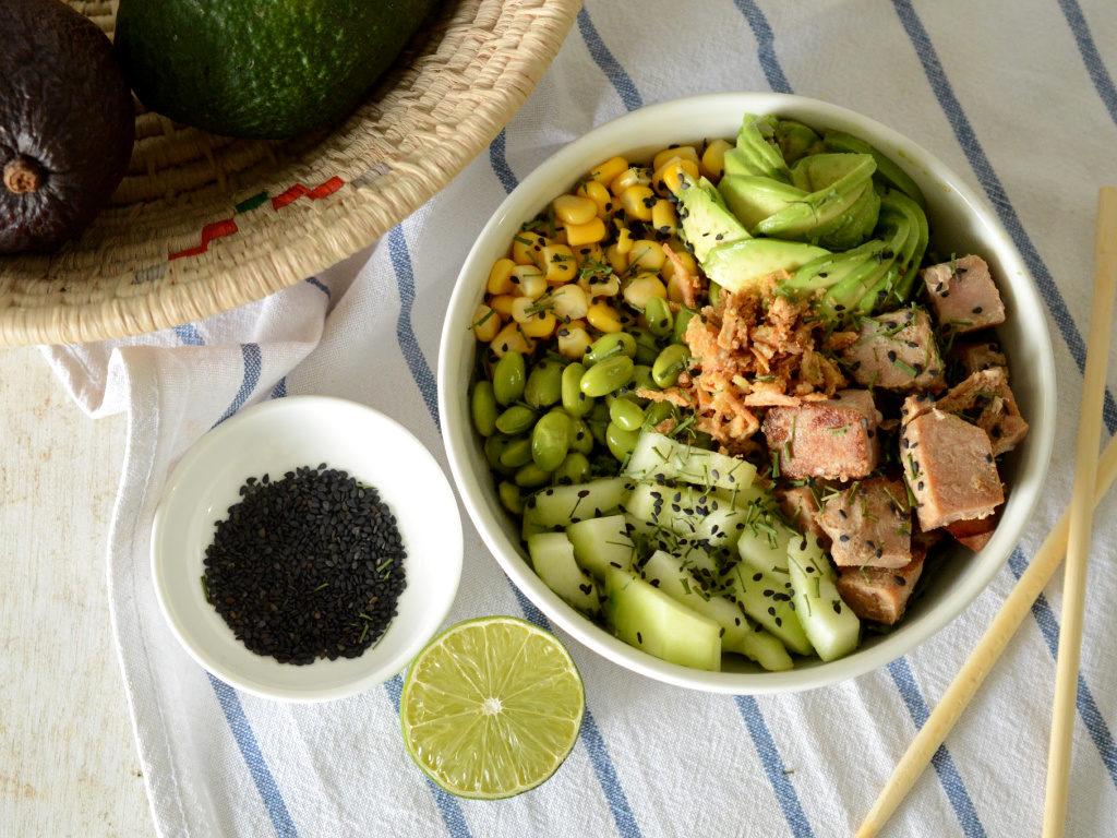 Foto de un tazón de poke de atún con pepino, semillas de soya, maíz, aguacate y cebolla crocante.