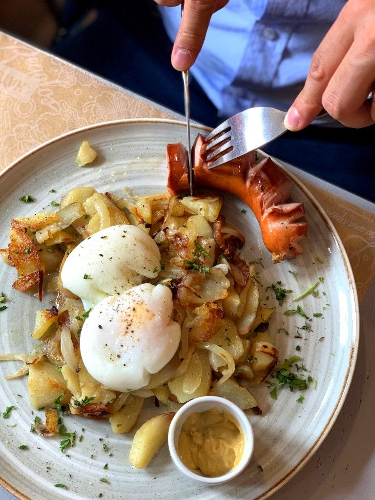 Plato con papas salteadas con cebolla, dos huevos pochados y una salchicha.