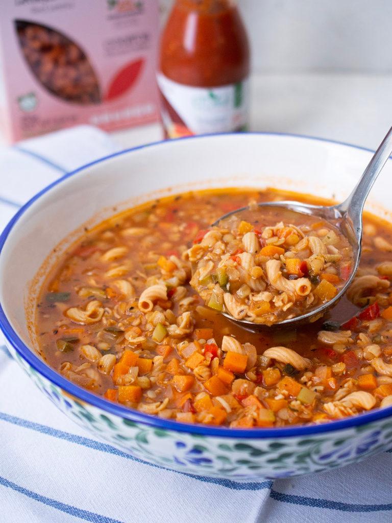 Detalle de la sopa de minestrone servida en un tazón grande con el cucharón.