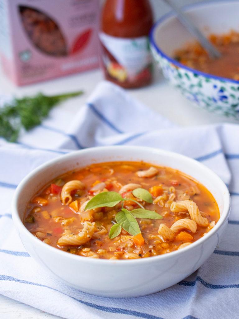 Un bowl de sopa de minestrone con hojas de albahaca.