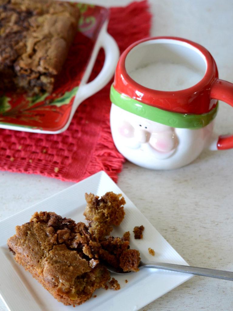 Porción de torta de manzana servida en un plato cuadrado con una cuchara.