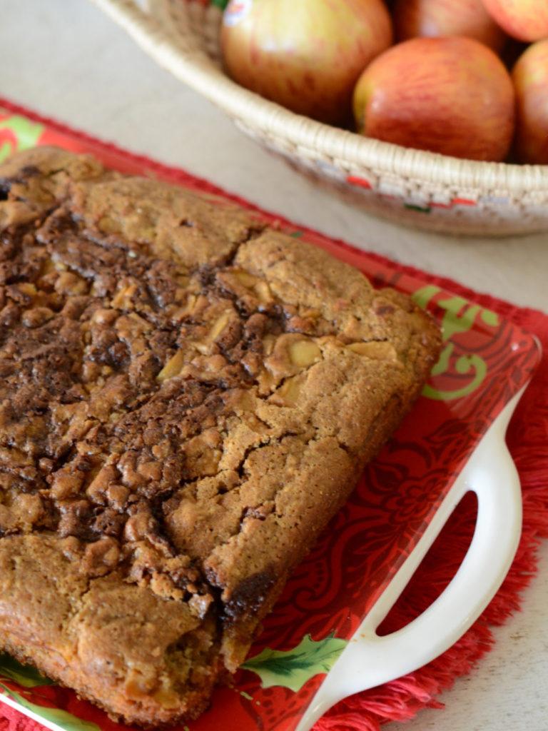 Torta de manzana y canela servida en un plato de Navidad, al fondo se ven manzanas rosadas en una canasta.