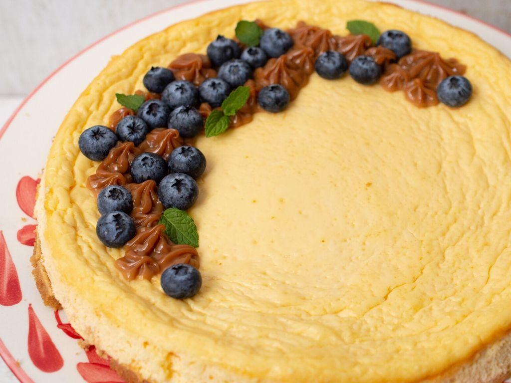 Plano cerrado del cheesecake saludable decorado con arándanos y arequipe.