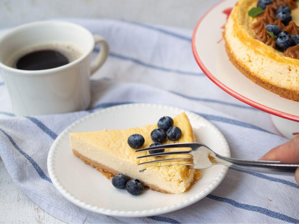 Un trozo de cheesecake saludable servido con arándanos y una taza de café color blanca.