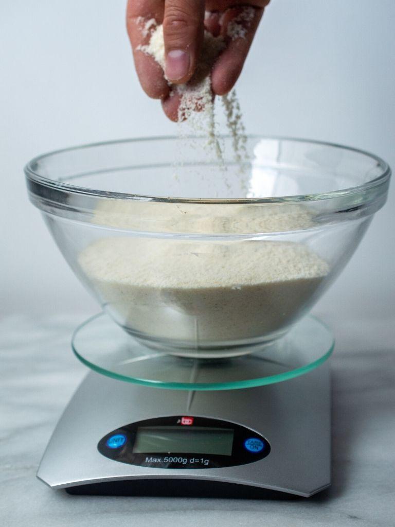 La harina de maíz para el bollo limpio casero servida en un tazón de vidrio sobre una báscula.