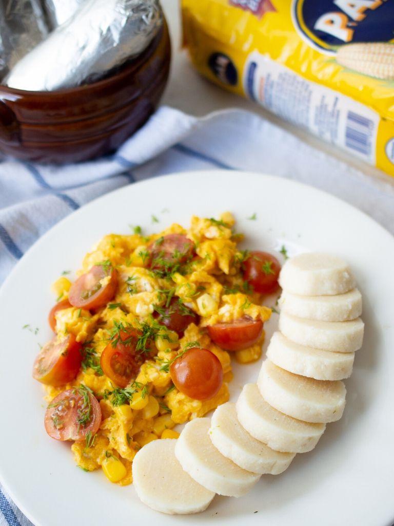 Plato con huevos revueltos y bollo limpio casero.