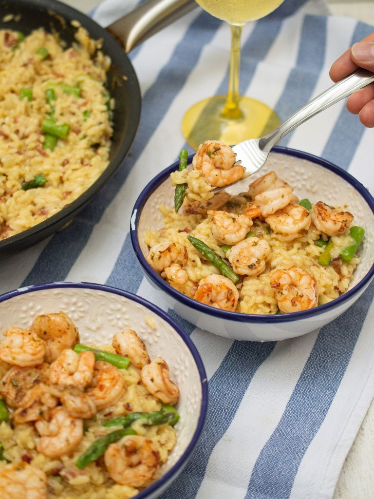 Tazón blanco con azul servido con risotto de camarones con espárragos.