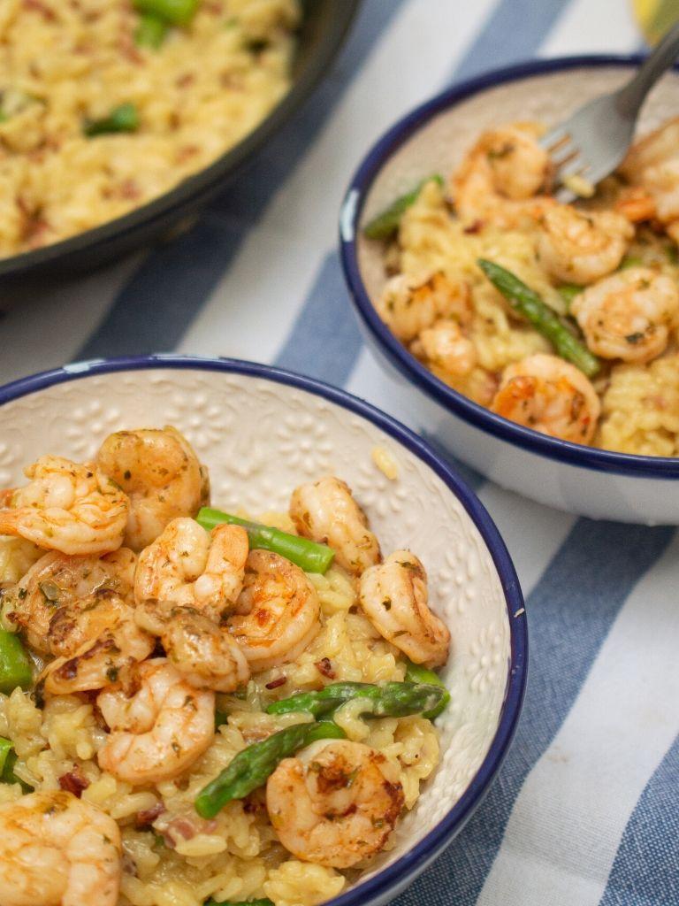 Plato de risotto de camarones y espárragos con un tenedor.