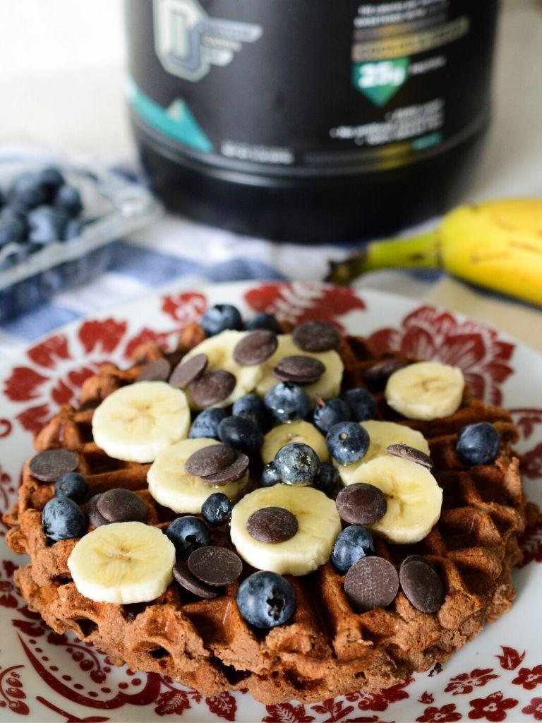 Waffle de proteína con banano, chocolate y arándanos.