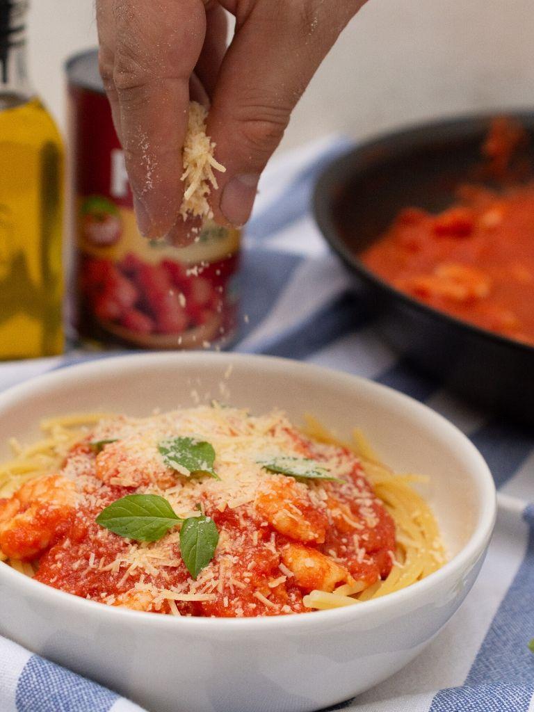 Plato blanco con spaghetti, con salsa roja. Pasta con camarones.
