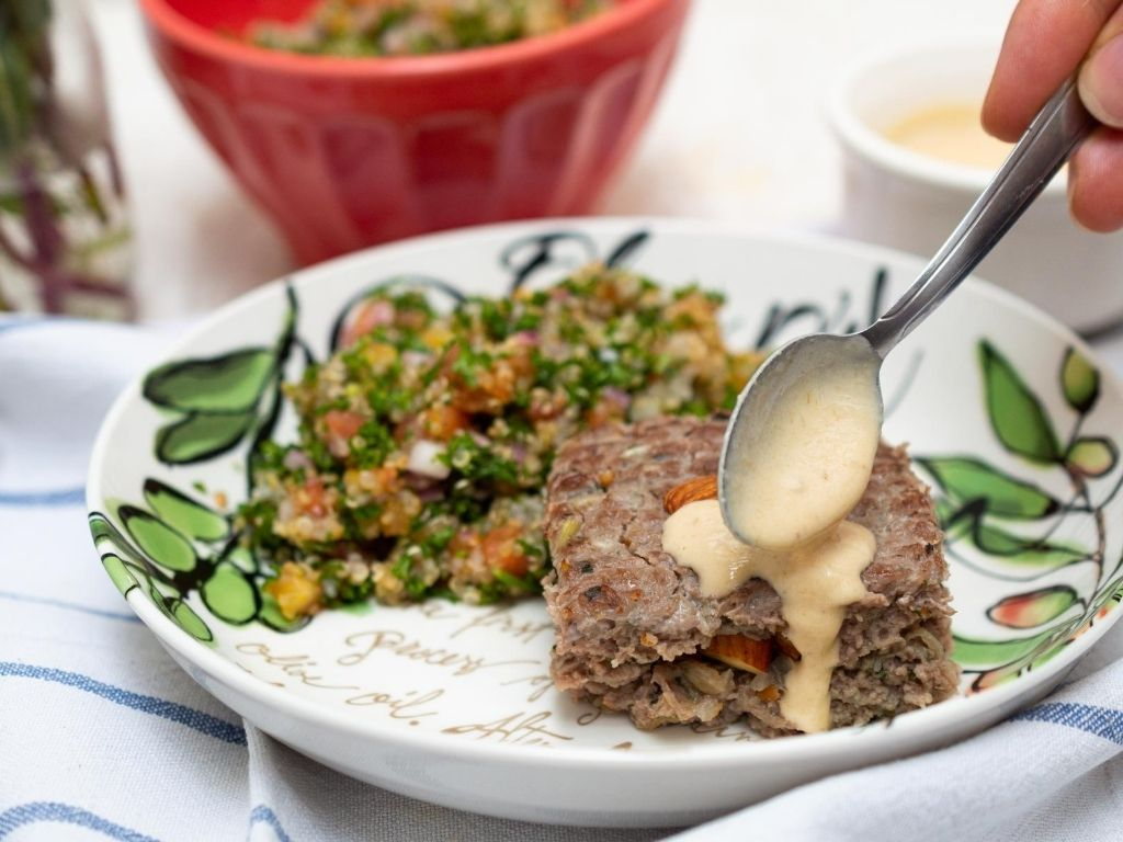 Plato blanco con una porción de ensalada servida y otra de kibbe asado, a este una cuchara le agrega una salsa blanca.