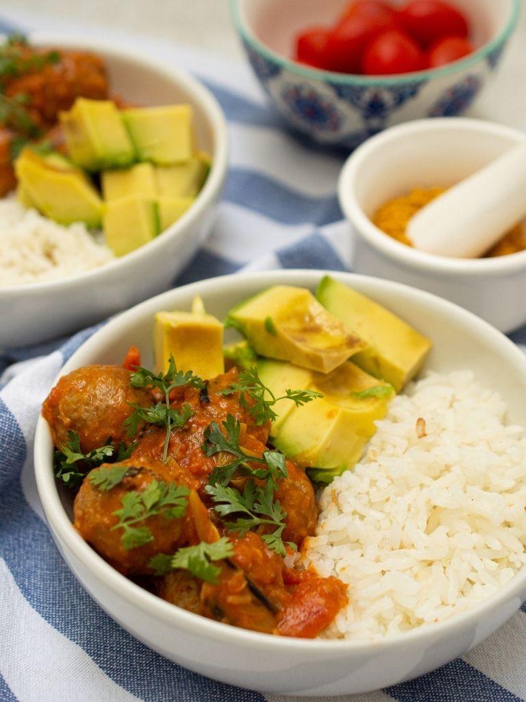 Bowl blanco sobre tela blanca con azul, servido con arroz, aguacate y albóndigas al curry.