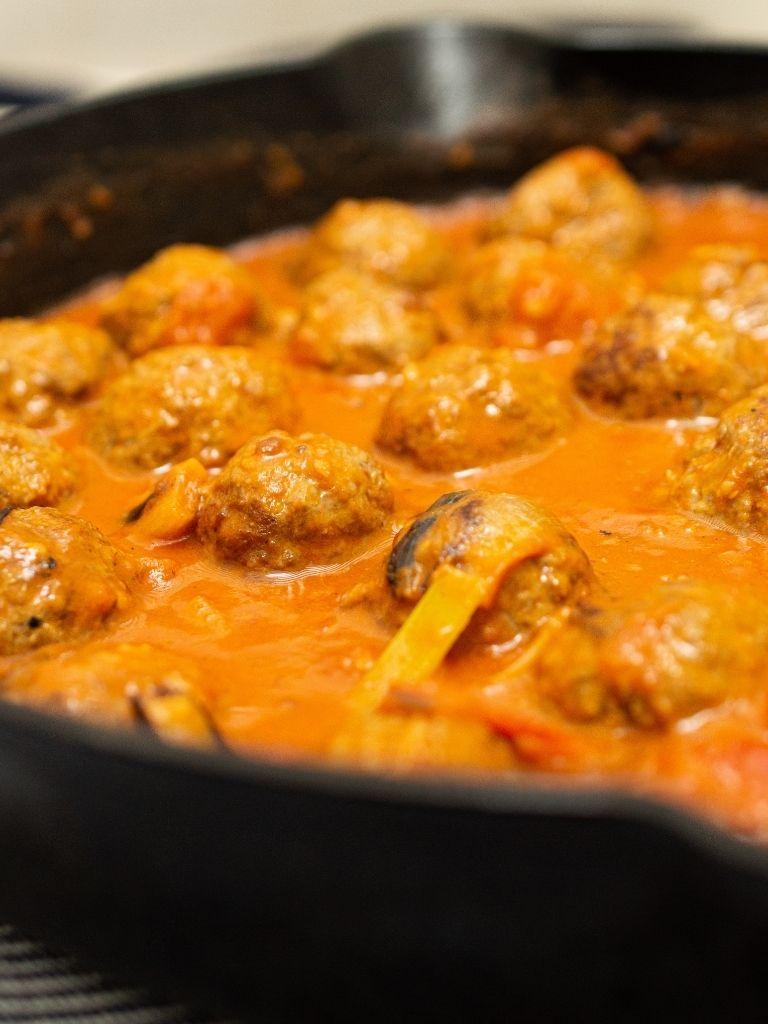 Primer plano de las albóndigas al curry en una sartén.