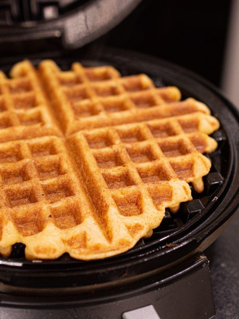 Plancha de wafflera color negro con un waffle de buñuelo color dorado recién preparado.