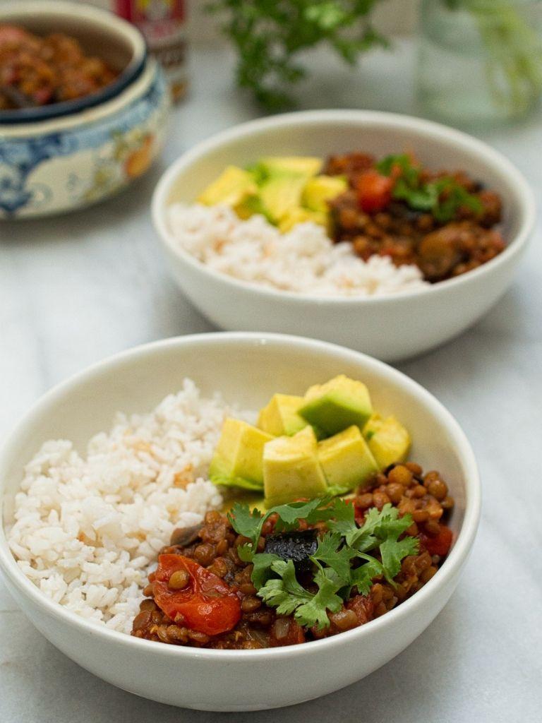 Plato blanco servido con guiso de lentejas con berenjena, arroz y aguacate.