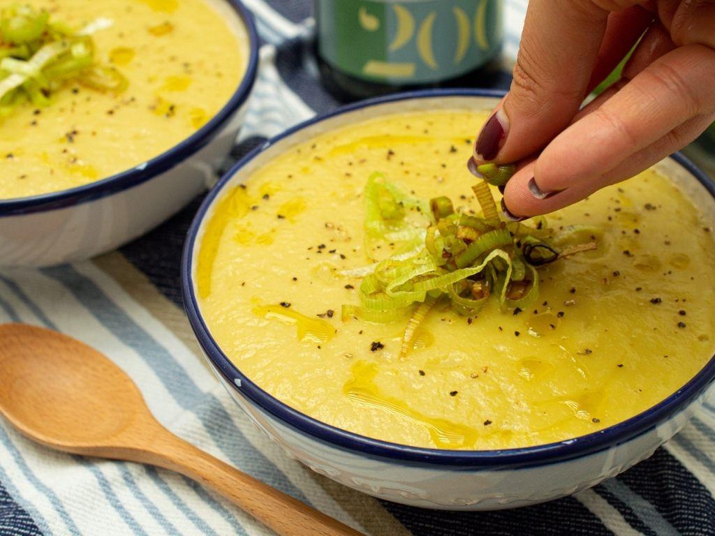 Tazón blanco con borde azul servido con una sopa color amarillo. Una mano sirve encima puerro frito.