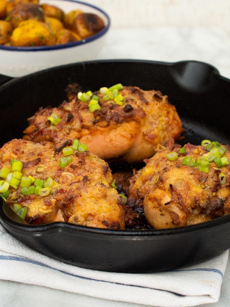 Pechuga gratinada ranchera servida en una cacerola de hierro, detrás, un bol con papas criollas.